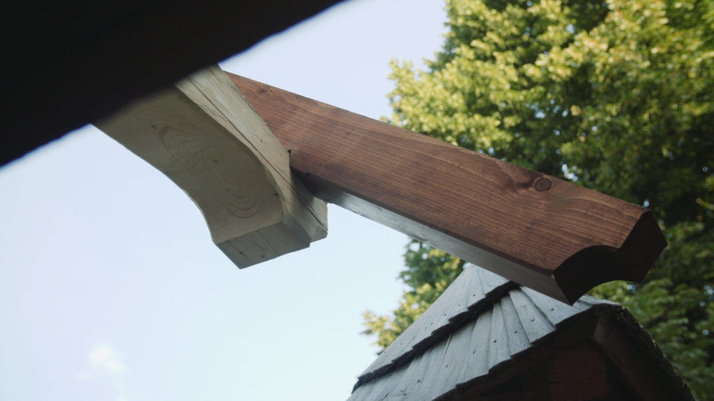 Detail zakončení ozdobné hlavice a krokve krovu.