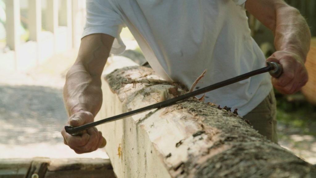 Tesař odstraňující kůrou ze stromu pomocí pořízu.