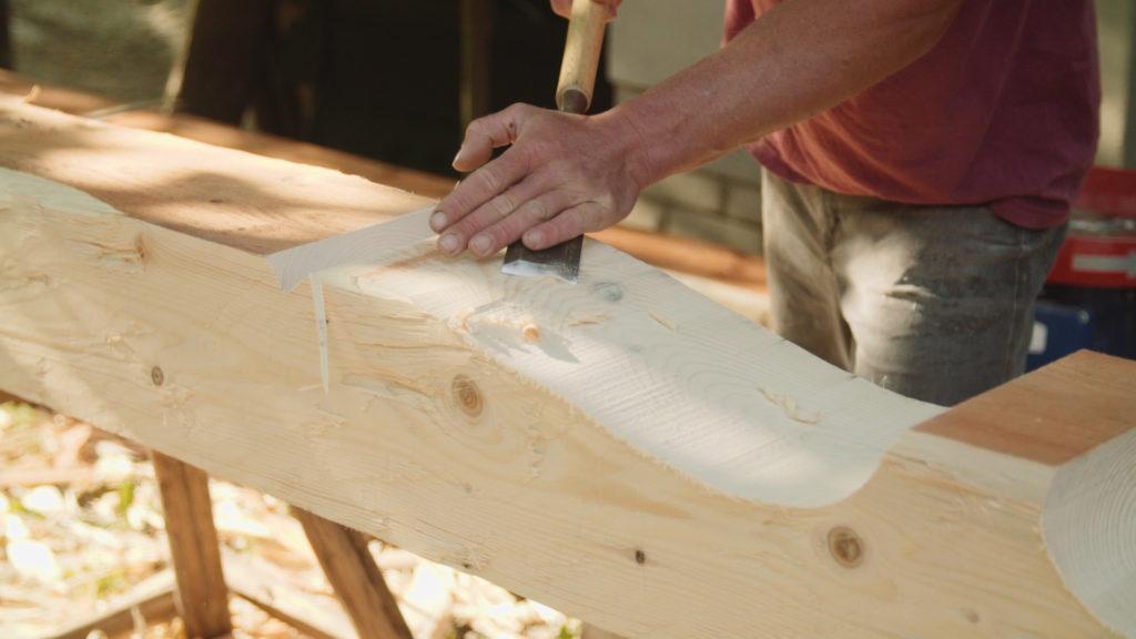 Tesař tvořící ozdobnou hlavici trámu.